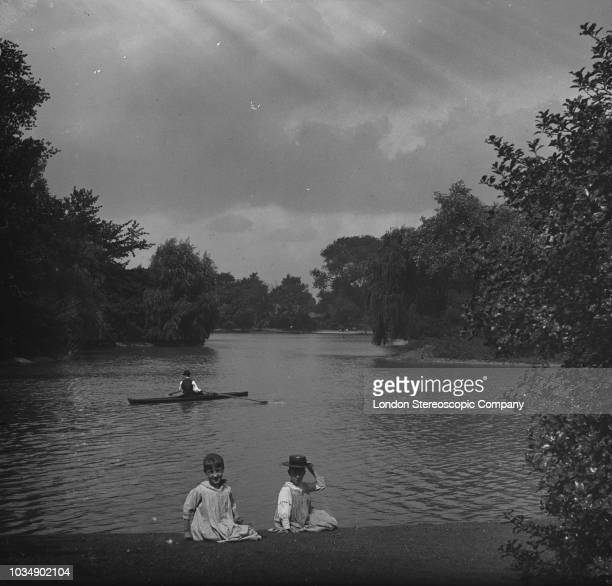 Two children on the bank of Battersea Park boating lake in south London, circa 1897.