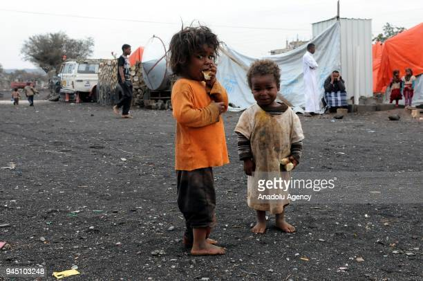 Two children one of them eating and the other one holding a bread are seen at Darwan refugee camp in Amran north of Sanaa Yemen on April 11 2018...