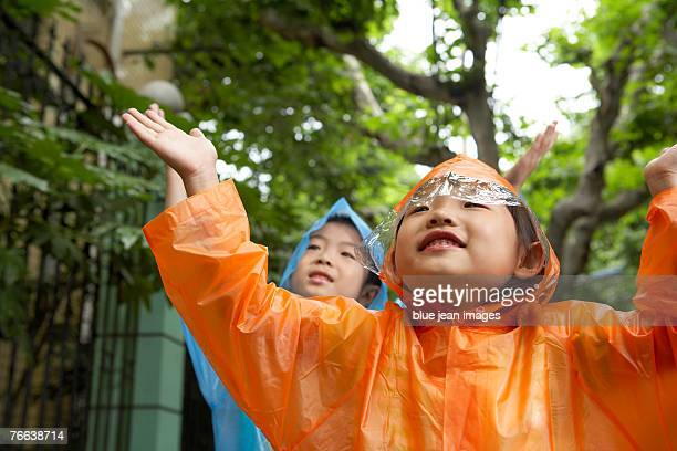 Two children outstretching their arms feeling for rain.