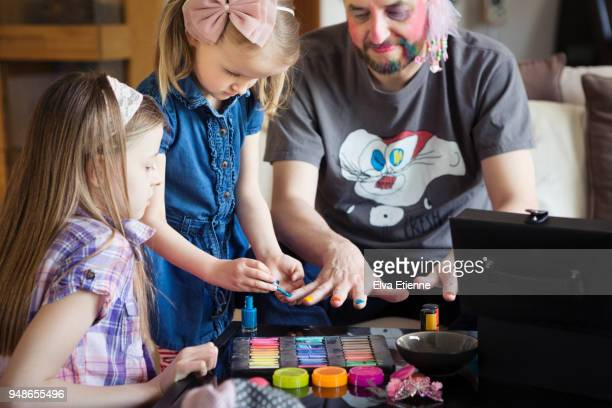 Two children painting their father's fingernails