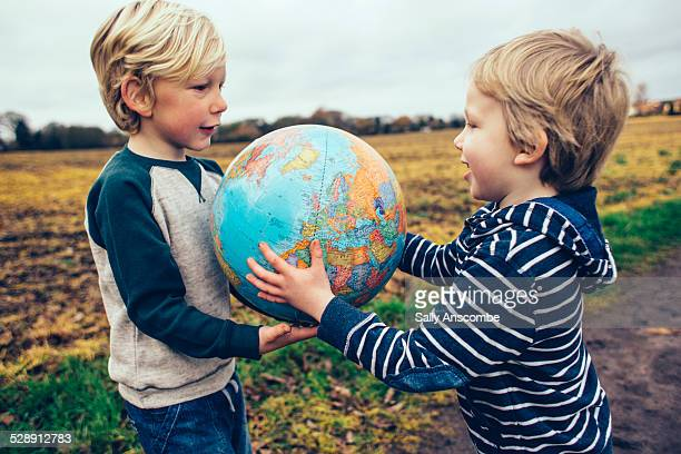 two children passing a globe to each other - world kindness day stock photos and pictures