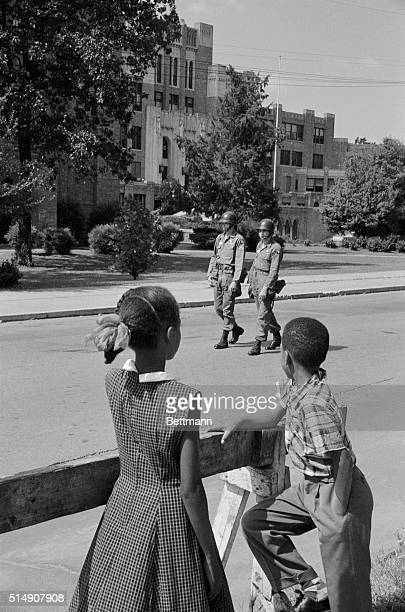 Two children pause on their way to church to watch two members of the National Guard patrol the Park Street entrance of Central High School where...