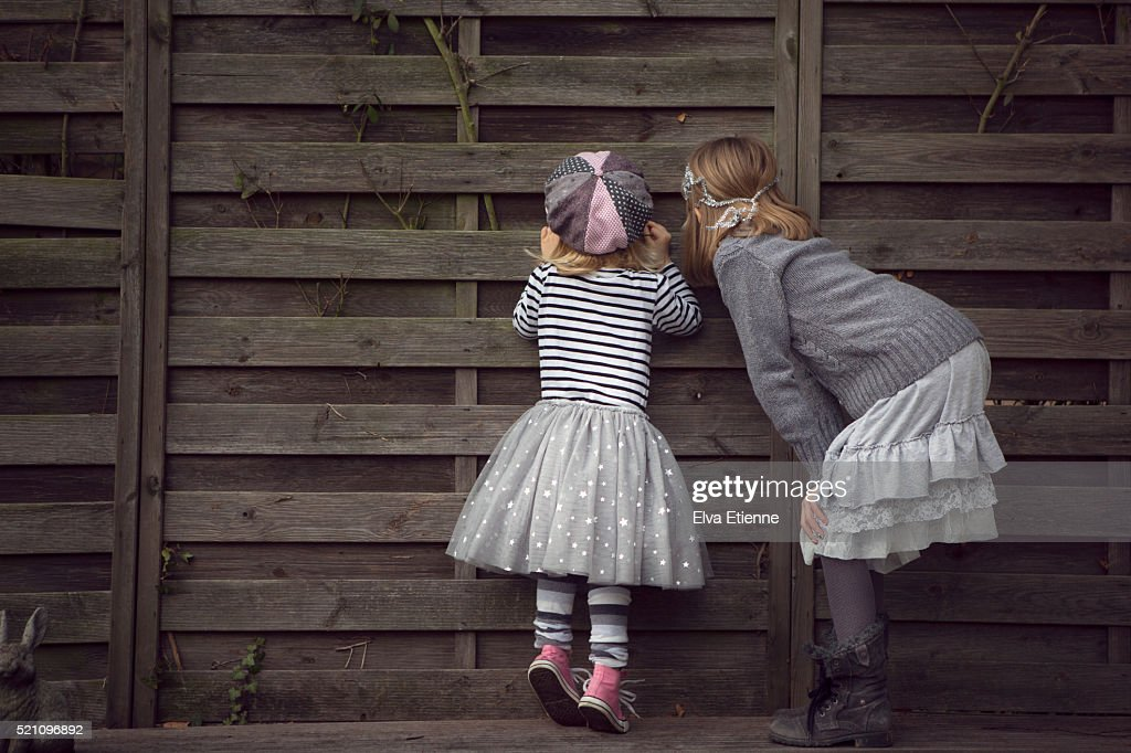 Two children peeking through hole in a fence : Foto de stock