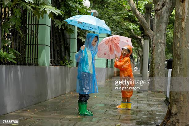 Two children play on a rainy day in Shanghai.