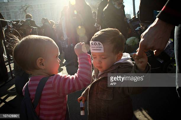 Two children play outside the Government's headquarters in Bucharest on December 8 2010 during a protest called by mothers to oppose a Labour...