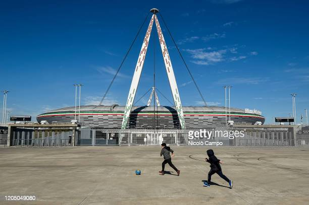 Two children play with a ball outside desert Allianz Stadium . The Italian Cup semifinal second leg football match between Juventus FC and AC Milan...