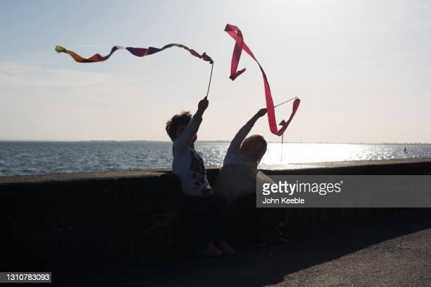 Two children play with their ribbon wands on a warm sunny Easter Sunday at Chalkwell beach on April 04, 2021 in Southend-on-Sea, England. Earlier...