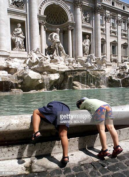 Two children play with water in the Trevi Fountain in Rome 04 August 1999 to refresh themselves as Italy is experiencing high summer tempertures