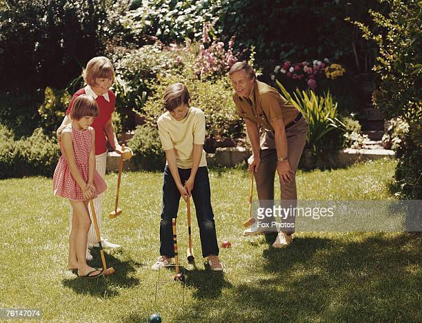 Two children playing croquet with their parents circa 1975