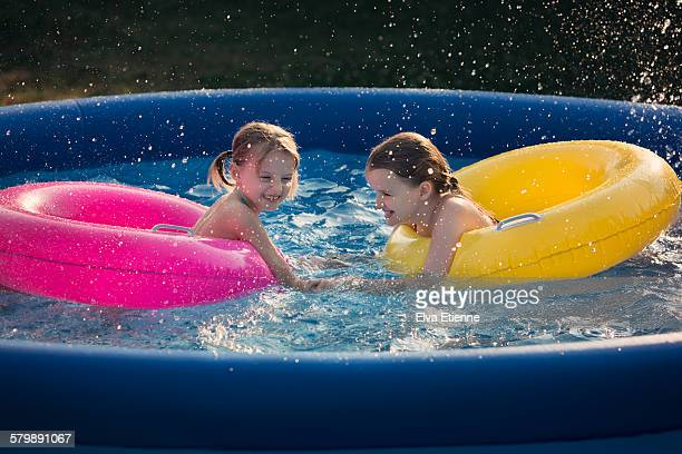 Two children playing in inflatable swimming pool