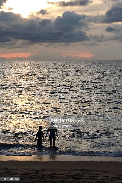 Two children playing in sea at sunset