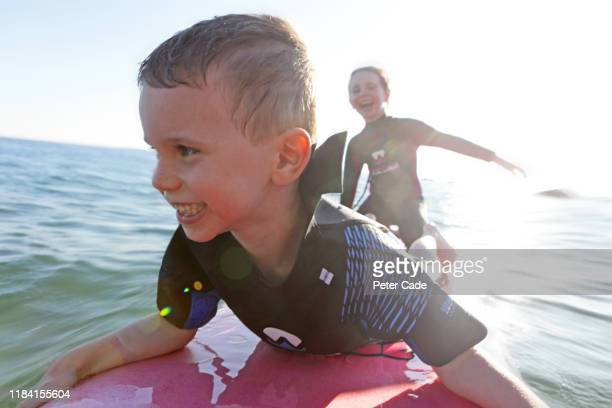 two children playing in sea on surfboard - vacations stock pictures, royalty-free photos & images