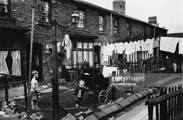 Two children playing in the back garden of their house in Salford. Original Publication: Picture Post - 8127 - The Housing Jungle - pub. 1955