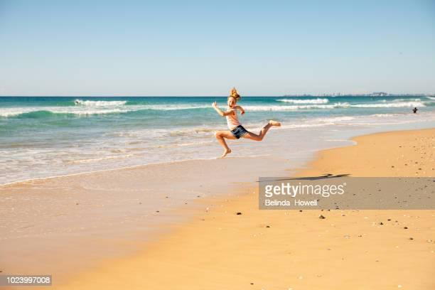 two children playing in the sand and water on a gold coast beach, queensland  australia - gold coast stock pictures, royalty-free photos & images