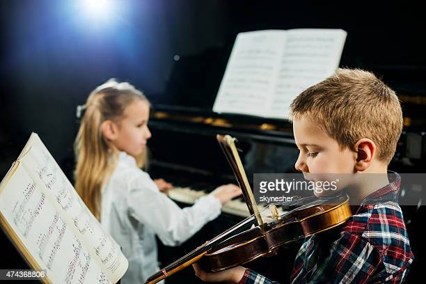 Two children playing musical instruments.