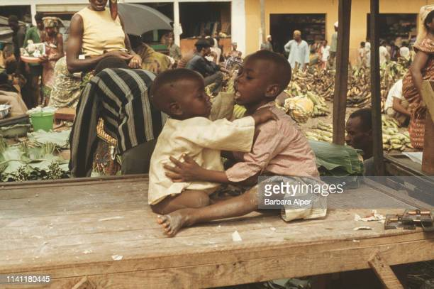 Two children playing near a market stall in Abidjan Ivory Coast February 1975