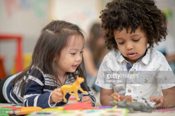 two children playing together - fatcamera stock pictures, royalty-free photos & images