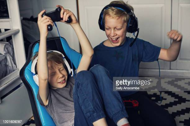 two children playing video games together - sally anscombe stock pictures, royalty-free photos & images