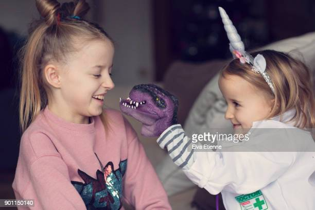 Two children playing with a toy dinosaur hand puppet
