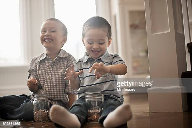 Two children playing with coins, dropping them into glass jars.