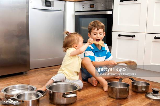 two children playing with cooking pan - percussion instrument stock pictures, royalty-free photos & images
