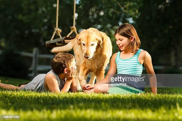 Deux enfants jouant avec un chien dans le jardin