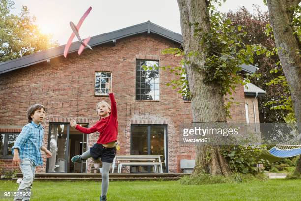 two children playing with toy airplane in garden of their home - middle class stock pictures, royalty-free photos & images