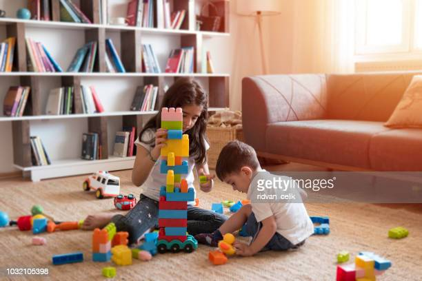 two children playing with toy blocks. - building blocks stock pictures, royalty-free photos & images