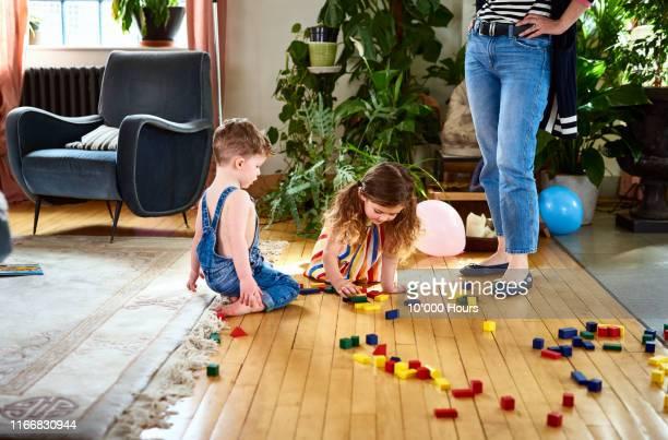 two children playing with wooden blocks on wooden floor - friendly match stockfoto's en -beelden