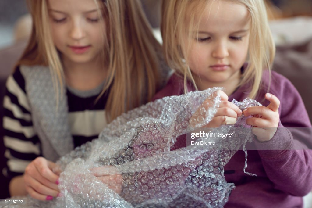 Two Children Popping Plastic Bubble Wrap High-Res Stock Photo - Getty Images