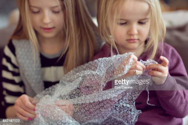 Two children popping plastic bubble wrap