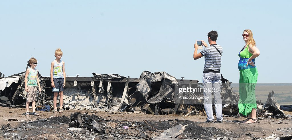 Two children pose for a photograph at the Malaysia Airlines flight MH17 crash site near the Grabovo town in Donetsk, Ukraine on July 26, 2014.