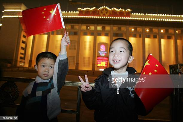 Two children pose in front of a countdown board for the Beijing 2008 Olympic Games in front of the National Museum in Beijing, China, April 29, 2008....
