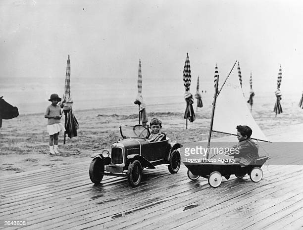 Two children racing each other in a toy car and boat along the beach front in Deauville