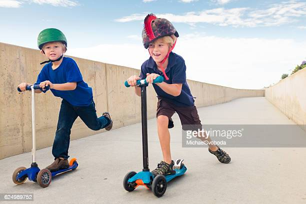Two Children Racing on Scooters