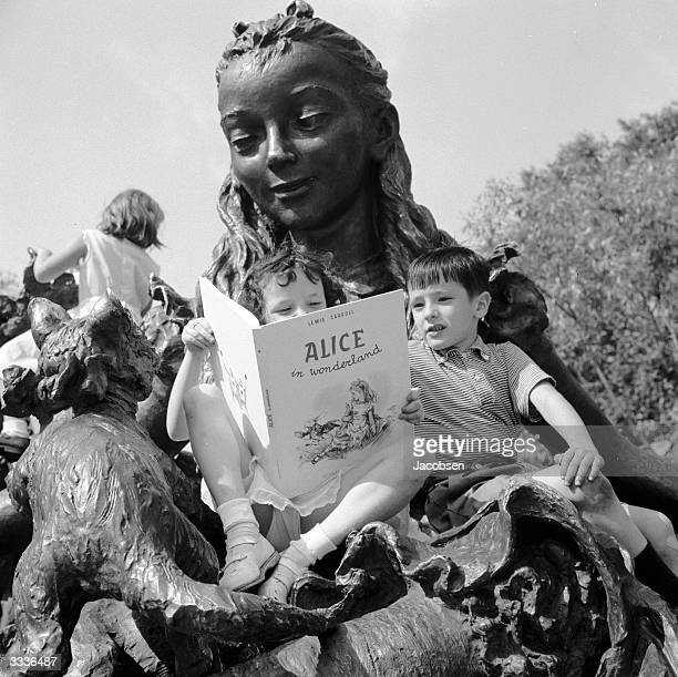 Two children read 'Alice In Wonderland' on a statue of Alice in New York's Central Park