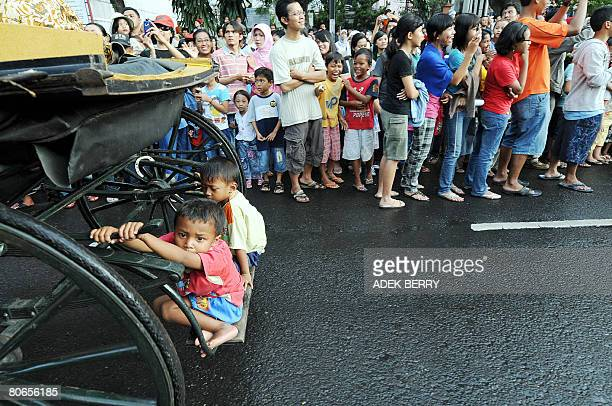 Two children ride on the undercarriage of a cart as it parades down a street during the Solo Batik Carnival in the central Java city of Solo on April...