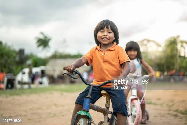 two children riding a bicycle in a rural place - south america stock pictures, royalty-free photos & images