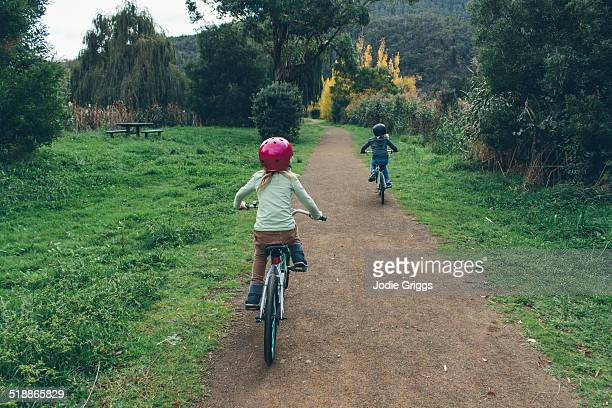 Two children riding bicycles along dirt path