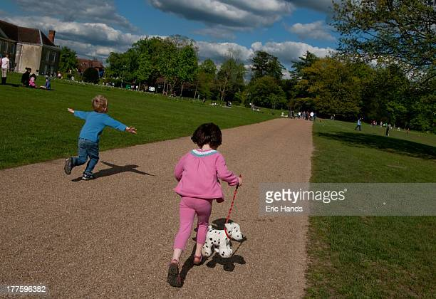 CONTENT] Two children run along a path in Priory Park Reigate The boy has his arms outstretched in a flying position and the girl is wearing a pink...