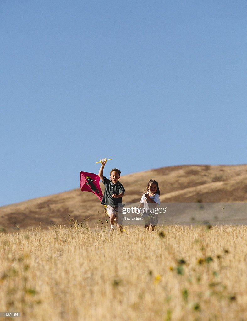 Two children run through a golden field with a kite : Photo