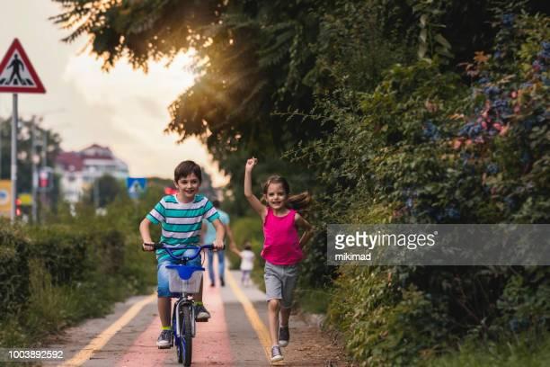 Deux enfants en cours d'exécution et de l'équitation bicykle ensemble