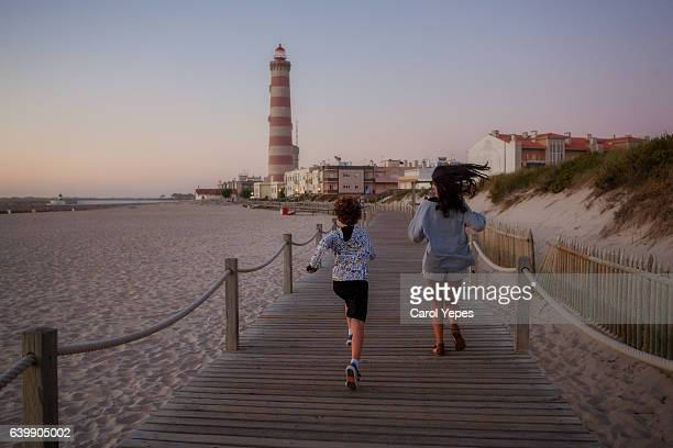 two children running away in beach to lighthouse