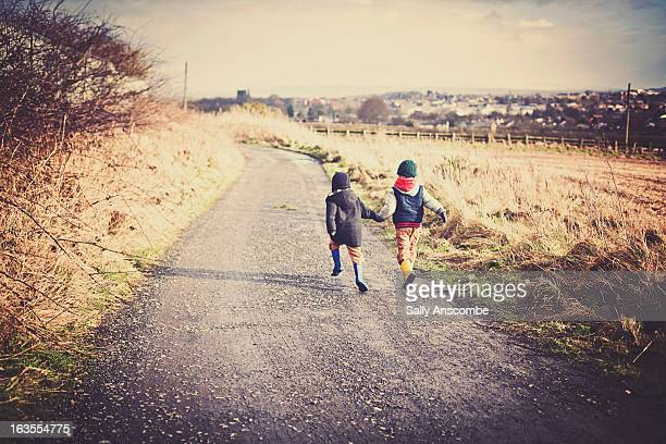 two children running down a country lane - only boys stock photos and pictures