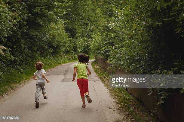 Two children running down a country lane