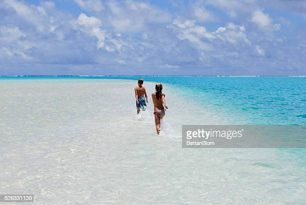 two children running on sandbar in ocean, aitutaki, cook islands - pacific islands stock pictures, royalty-free photos & images