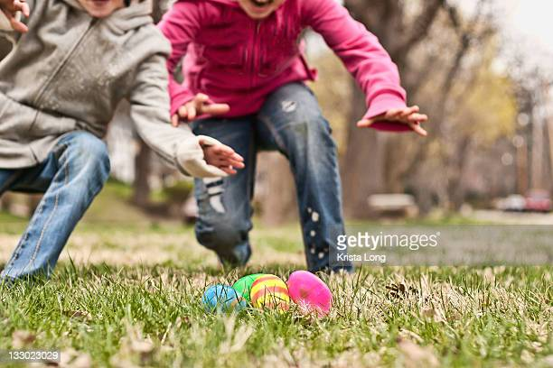 Two children running towards easter eggs