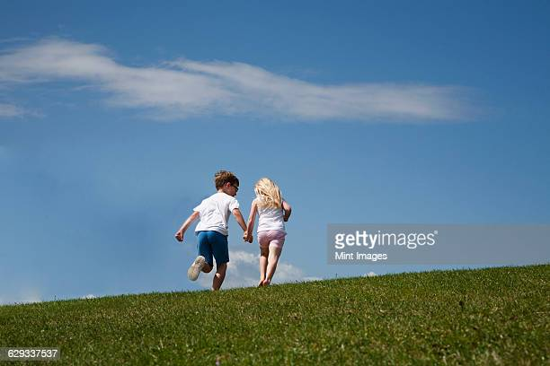Two children running up a hill