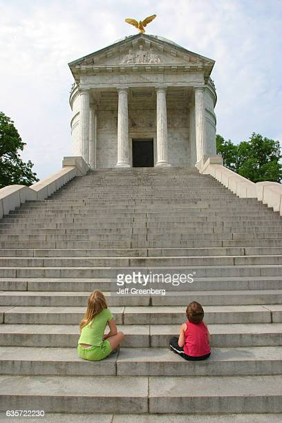 Two children sat on the steps looking at the Illinois Memorial