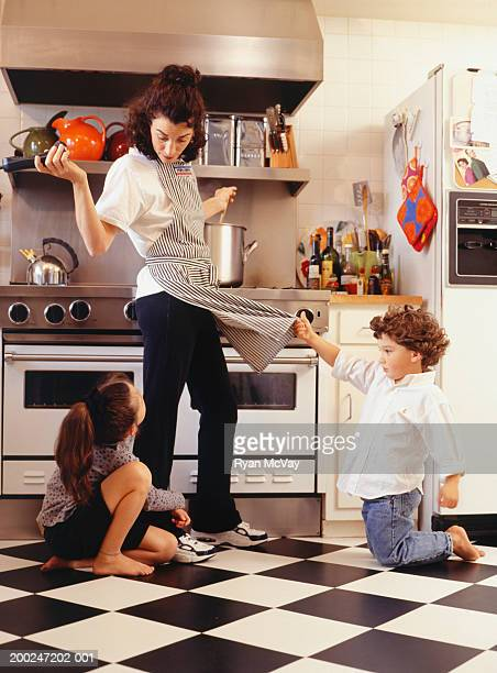 Two children (4-5) (6-7), seeking attention from mother in kitchen